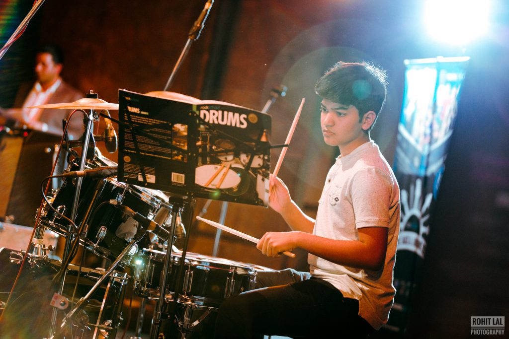 young drummer practicing with RSL book and Rockschool practice diary